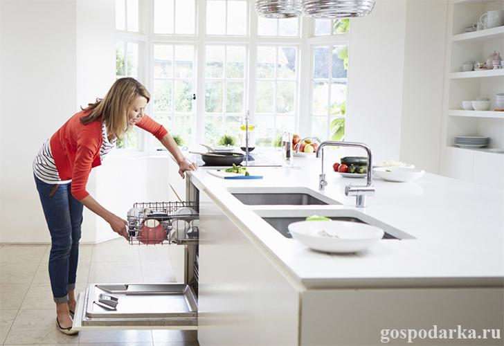 женщина загружает посудомоечную машину