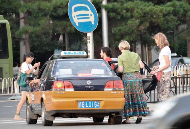 туристы садятся в такси в Китае